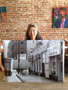 Nancy Sekizawa holding the image of The Atomic Café last located at First and Alameda in Los Angeles' Little Tokyo. Photo by Tadashi Nakamura