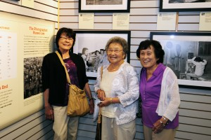 (From left) Anne Enoki, Rose Sorenson and Kay Yamaguchi stand in front of the image Russell Lee took of them in 1942, shown above. Photo by David Nishitani