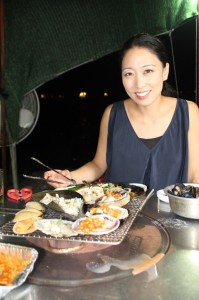 "Chef Judy Joo sits down for some grilled clams by the sea near Taejondae Resort Park in Busan for her new series ""Korean Food Made Simple."" Photo courtesy of  Blink Films/ Media Story 9 Prods"
