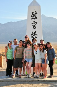 The group poses with Munteanu (left) in front of a monument in Manzanar cemetery. Photo by Ryan Kuramitsu