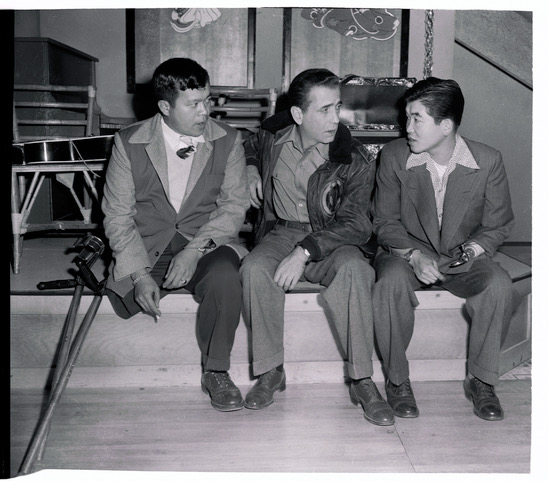 (Original Caption) Old friends meet again on the set of Tokyo Joe as Humphrey Bogart chats with two Nisei GI's he met during a wartime entertainment tour of Italy. Frank Fujino (left) and Don Seki (right), who fought with the most-decorated outfit in World War II, the 442nd Infantry Regiment. Both have speaking parts in Bogart's new picture.